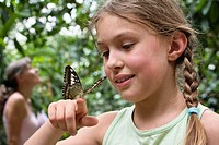 9 year old girl with butterfly on her hand, Germany, Europe