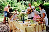 Grandfather Serenading Family at Outdoor Barbecue