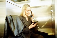 Businesswoman Using a PDA in Phone Booth