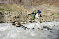 Woman crossing river on rocks, Photoksar, Zanskar Range Traverse, Zanskar Range, Zanskar, Ladakh, Jammu and Kashmir, India