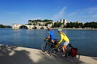 Cyclists in front of Saint Benezet bridge and the papal palace in Avignon, Provence, France