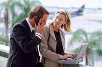 Businesspeople using cell phone and laptop