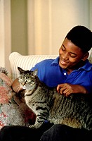 Teenage boy sitting on couch with cat