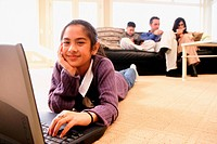 Smiling Girl with Laptop and Family in Background