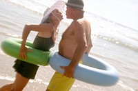 Couple on Beach with Inner Tubes