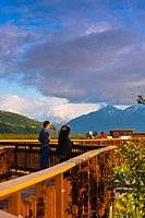 Visitors enjoy the view from the boardwalk at Potter Marsh with the Chugach Mountains in the background, Southcentral Alaska, Spring
