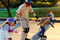 Father inline skating with kids