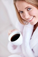 An attractive young woman holding a cup of coffee