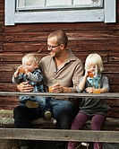 Father with two kids drinking juice in front of wooden house