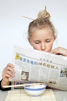 Girl with hair bun reading newspaper