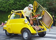 A BMW Isetta 250 being driven in a parade for the Comox Aquatic Days festival has stopped and is showing how a passenger gets out