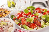 An assortment of salads on a buffet table  Potato salad, bean salad and fresh mixed salad arranged on a white table with glasses, cutlery and plates  ...