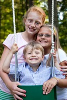 Two Smiling Girls Posing With Young Boy in Swing, Close_Up
