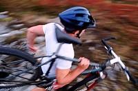 Mountain biker running while carrying bike