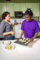 Assisted by a teacher, a blind African-American preteen girl makes rolls by touch from prepared dough in a cooking and baking class at the Blind Child...