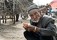 Old Uighur man eating watermelon, Kashgar, Xinjiang Province, China