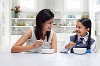Mother and daughter at table eating breakfast