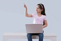 Little girl with a laptop pointing