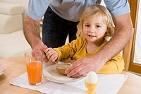 Father spreading butter on bread for daughter breakfast