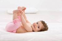 Baby girl lying on back, smiling, portrait