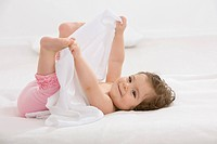 Baby girl lying on back and holding toes, smiling