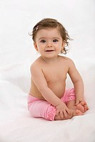 Baby girl sitting on baby blanket, smiling, portrait