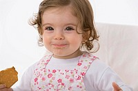 Baby girl eating cookie, smiling, close up
