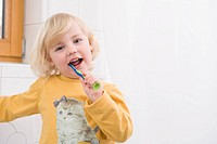 Girl brushing her teeth in bathroom, close up, portrait (thumbnail)