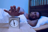 Man turning off alarm clock (thumbnail)