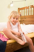 Girl putting socks, smiling, portrait