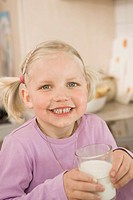 Girl drinking glass of milk, smiling, portrait