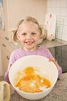 Girl holding bowl of egg yolk and flour, smiling, portrait