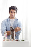 Portrait of handsome young man holding paintbrush in art studio