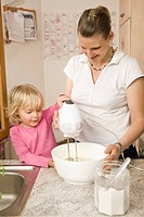 Mother and daughter mixing batter with electric whisk