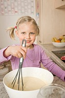Girl mixing batter in bowl, smiling, portrait