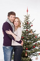 Mid adult couple embracing, Christmas tree in background, smiling, portrait