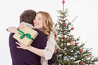 Mid adult couple embracing, while woman holding christmas gift