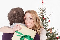 Mid adult couple embracing, while woman holding christmas gift, smiling