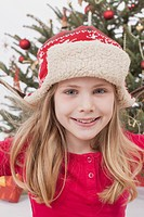 Girl with Santa hat, Christmas tree in background, smiling, portrait