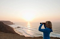 Portugal, Algarve, Sagres, Senior woman looking at beach through binocular