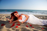 Young woman laying at the beach on sand with rose petals around her body