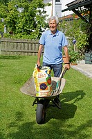 Germany, Bavaria, Senior man with wheelbarrow in garden