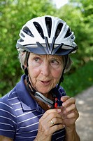 Germany, Bavaria, Senior woman with bicycle helmet, close up