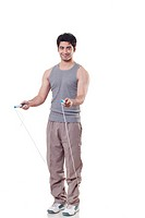 Full length portrait of a young man with skipping rope over white background