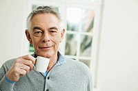 Germany, Berlin, Senior man with coffee cup, portrait