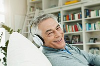 Germany, Berlin, Senior man with head phones on couch, portrait