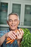 Germany, Berlin, Senior man holding carrots, portrait
