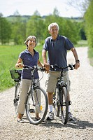 Germany, Bavaria, Senior couple with bicycle, smiling