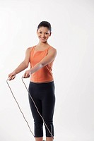 Portrait of a young woman with skipping rope over white background