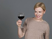 Mature woman with wine glass, smiling